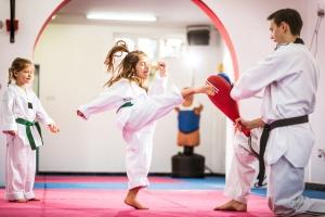 Two cute girls on taekwondo training, kicking and learning self-defence